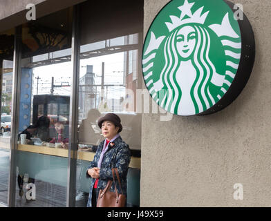 Nagasaki, Japan - March 26th, 2017: A japanese senior woman looking away outside the Startbucks Coffee in Nagasaki. - Stock Photo