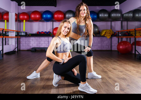 Two smiling fitness girls standing on the floor in the gym - Stock Photo
