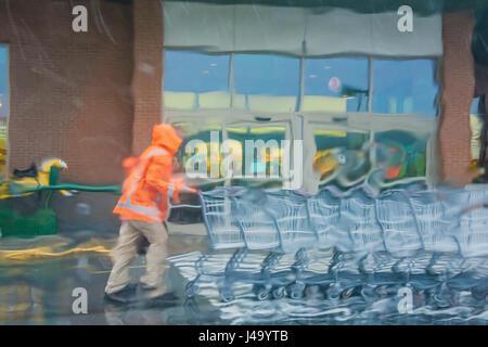 Rain warped view of parking lot attendant pushing shopping carts back to store - Stock Photo