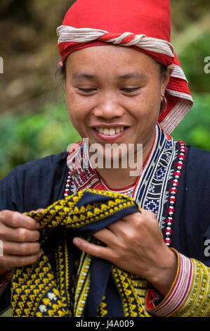 SAPA, VIETNAM - CIRCA SEPTEMBER 2014:  Young woman from the Red Dao minority smiling in Ta Phin Village near Sapa, - Stock Photo