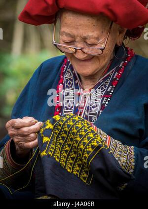 SAPA, VIETNAM - CIRCA SEPTEMBER 2014:  Old woman from the Red Dao minority knitting in Ta Phin Village near Sapa, - Stock Photo