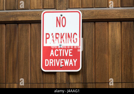 A no parking sign on a wooden door of a garage - Stock Photo