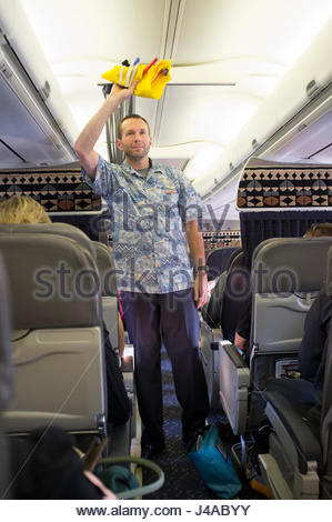 Caucasian male flight attendant demonstrating the use of the inflatable life vest during the safety briefing aboard - Stock Photo