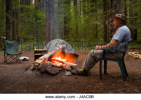Man sitting next to camp fire at Lower Falls Campground in the Gifford Pinchot National Forest, Skamania County, - Stock Photo