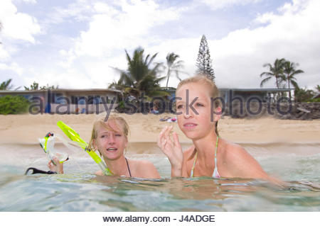 Sisters talking with each while in the warm waters of the Pacific Ocean off Mokuleia Beach, Oahu, Hawaii, USA - Stock Photo