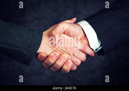 Joint enterprise handshake over business agreement, male and female businesspeople shaking hands after forming a - Stock Photo