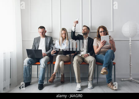 Group of young creative people sitting on chairs in waiting room - Stock Photo