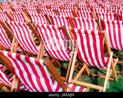 Rows of red and white striped wooden deckchairs lined up for an outdoor concert, viewed from behind - Stock Photo