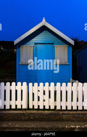 Blue and white beech hut at night, illuminated by street lamp, on the promenade at Westward Ho!, Devon, UK - Stock Photo