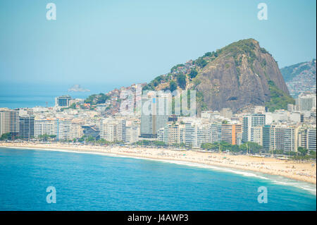 Bright scenic view of the golden crescent of Copacabana Beach with the city skyline of Rio de Janeiro, Brazil - Stock Photo