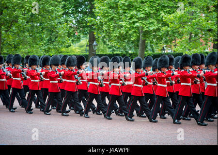 LONDON - NOVEMBER 20, 2016: Royal guards in traditional red coats and bear fur busby hats march in formation on - Stock Photo