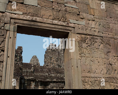 Bass relief of a battle scene on the outside wall, and a view through a doorway of the Bayon temple, Angkor Wat - Stock Photo