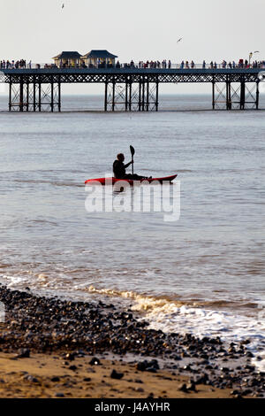 Cromer Pier on the North Norfolk coast England UK built in 1902 with man in kayak in foreground - Stock Photo