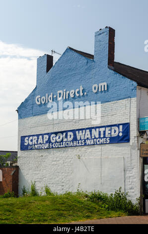 Large sign on building wall saying scrap gold wanted - Stock Photo