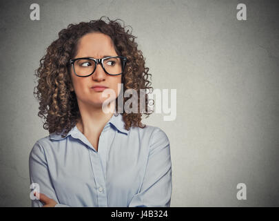 Displeased suspicious young woman with glasses looking sideways isolated on grey wall background. Negative face - Stock Photo