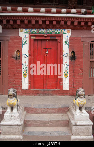 Red door with guardian lions and a a decorative surround, entrance to a house in Patan or Lalitpur Kathmandu, Nepal - Stock Photo