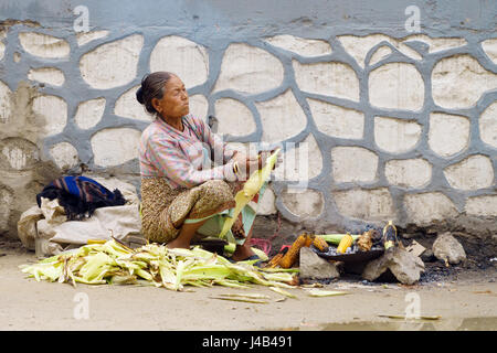 Old indigent woman roasting corn on the side of the street in heavily polluted air. Kathmandu, Nepal. - Stock Photo