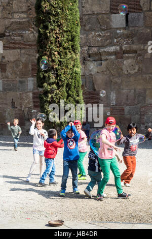 Children playing with large soap bubbles. - Stock Photo