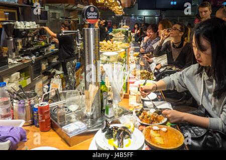People sitting at the bar eating seafood tapas in Mercat de Sant Josep de la Boqueria, Barcelona Spain. - Stock Photo