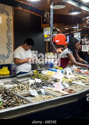 A man and a woman behind the counter of a seafood stall in Mercat de Sant Josep de la Boqueria, Barcelona Spain. - Stock Photo