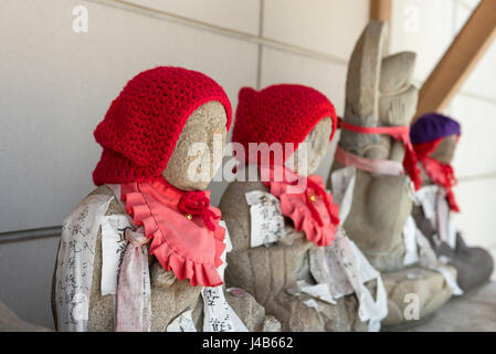 Statuettes wearing red woollen hats outside a Buddhist temple in Narita - Stock Photo