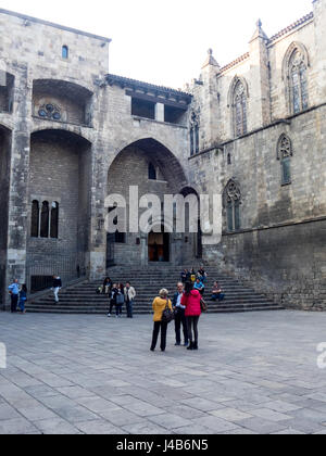 People sitting the steps leading to the Saló del Tinell and the Chapel of St. Agatha at Placa del Rei, Barcelona, - Stock Photo