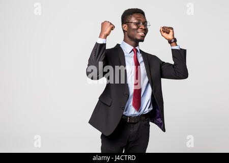 Very excited African business man with his arms in the air isolated grey - Stock Photo
