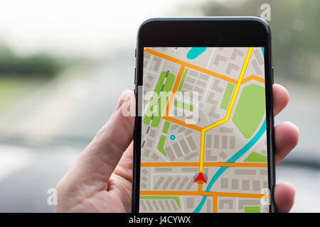 GPS Navigation on Mobile Phone Device and Transportation Concept. Male Hand Using Navigation System Map Tracking - Stock Photo