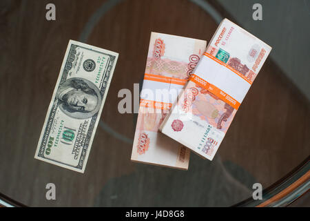 Russian Ruble and and US Dollars on wooden background - Stock Photo