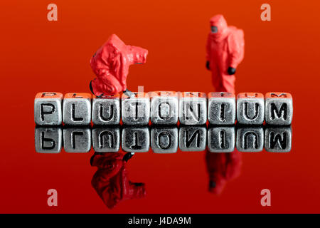 Miniature scale model team in chemical suits with the word plutonium on beads - Stock Photo