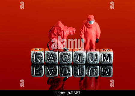 Miniature scale model team in chemical suits with the word radium on beads - Stock Photo