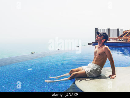 Side view of young man on vacation dangling legs in infinity swimming pool - Stock Photo