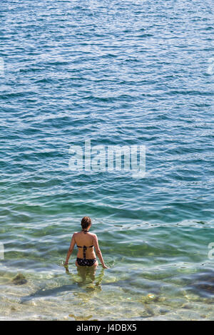 A young woman begins to cool off as she wades out into the clear waters in the Bay of Kotor. - Stock Photo