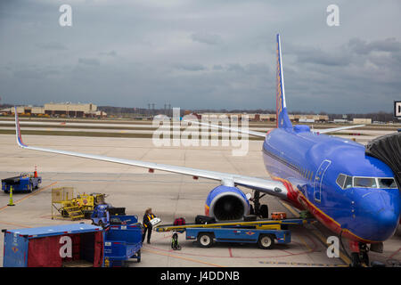 Detroit, Michigan - A woman loads baggage onto a Southwest Airlines plane at Detroit Metro Airport. - Stock Photo