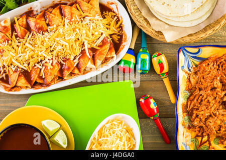 Homemade chicken enchiladas in a white casserole dish. - Stock Photo