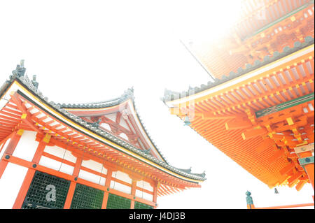 Low angle view of Japanese architecture buildings and roof details of pagoda against white sky at a Buddhist temple - Stock Photo