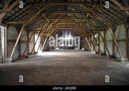Empty rural barn with wooden supports and remains of hay on the floor - Stock Photo