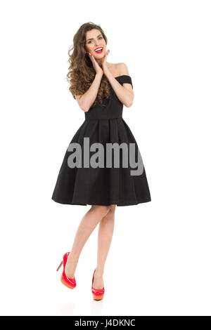 Beautiful young woman in elegant black cocktail dress and red high heels is standing on one leg, holding head in - Stock Photo