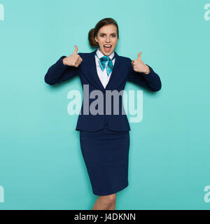 Excited stewardess in blue formal wear is standing with hands raised, showing thumbs up, shouting and looking at - Stock Photo