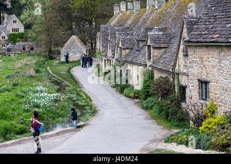 Tourist taking selfie in Arlington Row, Cotswold stone cottages, Bibury, Gloucestershire, England, UK - Stock Photo