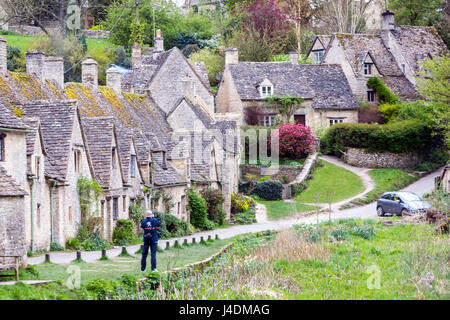 Tourist taking a picture to Arlington Row with the ugly car in  Cotswold stone cottages, Bibury, Gloucestershire, - Stock Photo