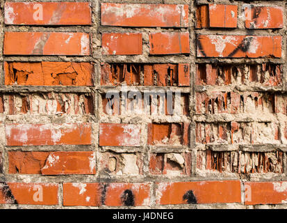 A fragment of a wall from an old red partially destroyed clay brick - Stock Photo