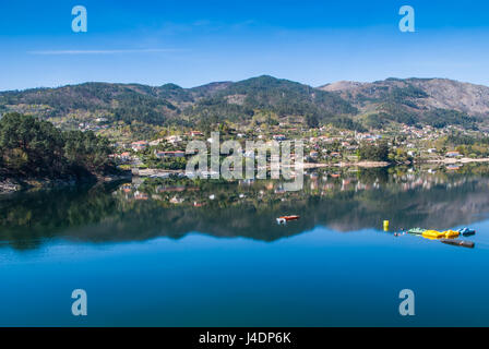 The water dam reflects the spring's sky and mountain colourfuness - Stock Photo