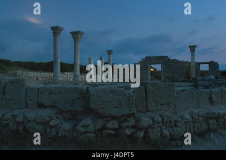 Columns and ruins of the ancient temple in Chersonese: night photography, in the sky a white glare from the moon, - Stock Photo