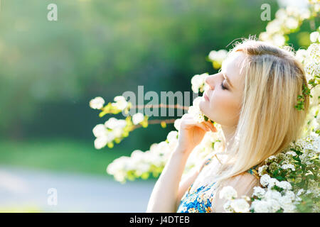 Beautiful young woman standing in a white flowered spring garden. - Stock Photo