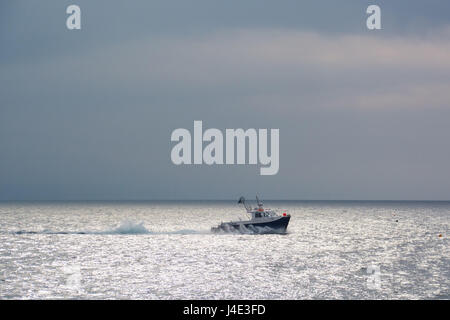 Mousehole, Cornwall, UK. 12th May 2017. UK Weather. The sunshine manages to break through the dark skies briefly at Mousehole, after overnight showers. Feeling humid, thundery showers are forecast for later. Seen here a fishing boat heading out for the morning. Credit: Simon Maycock/Alamy Live News