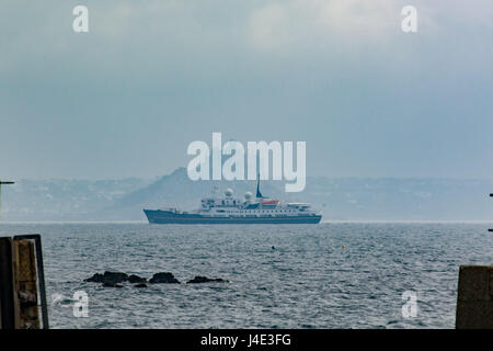 Mousehole, Cornwall, UK. 12th May 2017. UK Weather. The sunshine manages to break through the dark skies briefly at Mousehole, after overnight showers. Feeling humid, thundery showers are forecast for later. Seen here  a cruise ship heading past St MIchaels mount bringing visitors to Cornwall for the day. Credit: Simon Maycock/Alamy Live News