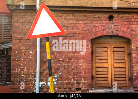 Empty Street sign in front of an ancient red brick wall with closed wooden window. - Stock Photo