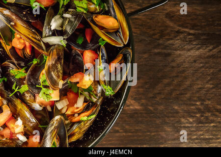 A closeup of a skillet of marinara mussels, shot from above on a dark rustic background with a place for text - Stock Photo