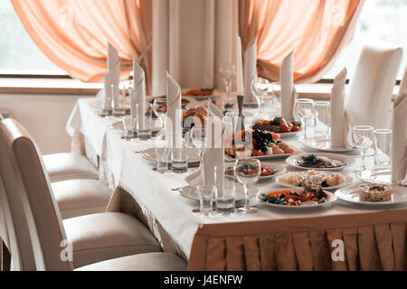 Wine glasses, napkins and fruit on the table for the banquet. - Stock Photo